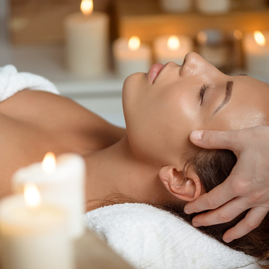 Young beautiful brunette girl having face massage relaxing in spa salon. Eyes closed. Copy space.