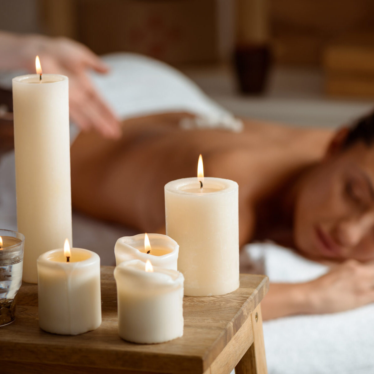 Young beautiful brunette girl relaxing in spa salon. Eyes closed. Focus on candles. Copy space.